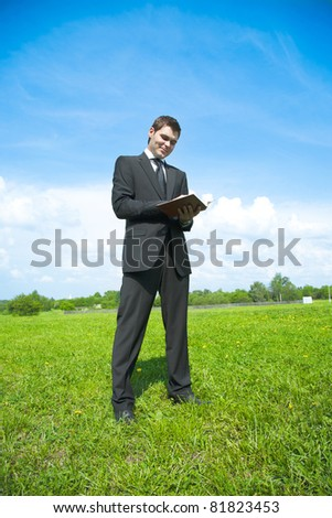young adult businessman in a suit, standing in a meadow with notebook in hand and make it write - stock photo