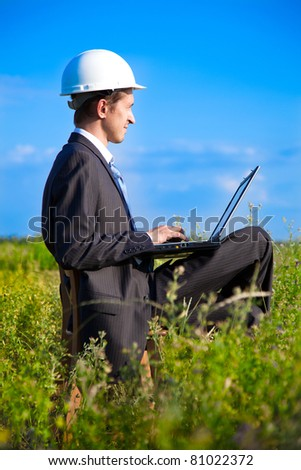 young adult businessman wearing a helmet sitting in a box on a chair with a laptop. focus on businessman - stock photo