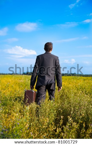 young adult businessman with old two suitcases businessman in the field - stock photo