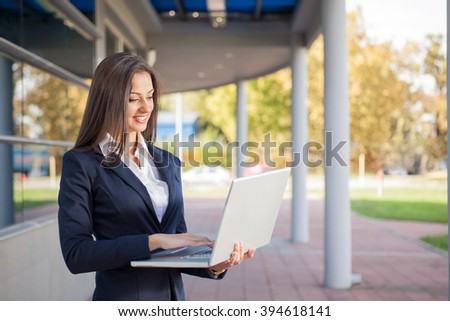 Young adult businesswoman using laptop outdoors - stock photo