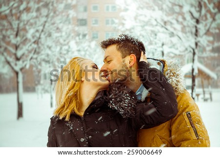 Young adult caucasian coupl in love kissing each other outdoors. Horizontal color photo - stock photo