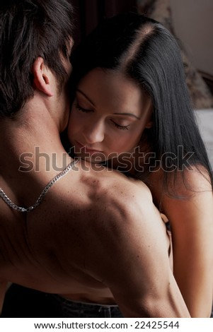 Young adult Caucasian couple in passionate embrace and undressing each other during sexual foreplay - stock photo