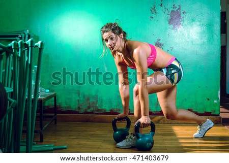 Young adult caucasian girl doing lunge exercise indoor with kettlebell.