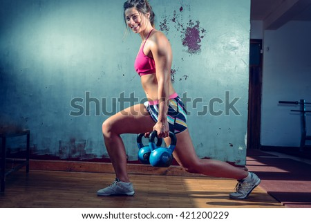 Young adult caucasian girl doing lunge exercise indoor with kettlebell. Toned Image. - stock photo