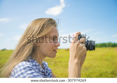 Young adult caucasian girl taking photo on retro vintage camera against blue sky with clouds and summer field Cute woman photographer stand outdoor Empty space for inscription  - stock photo