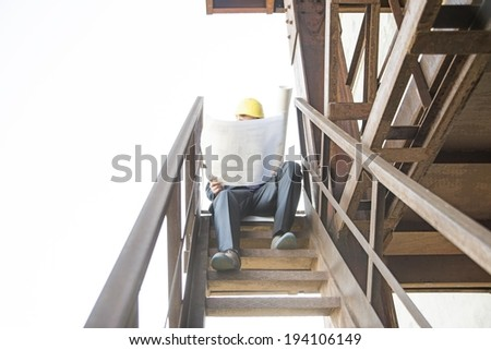 young adult caucasian male architect in yellow hardhat looking paper plan blueprint documents. Horizontal shape Well dressed engineer sitting on metal rusty ladder - stock photo