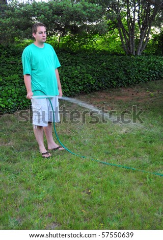 Young adult Caucasian male holds a hose and waters his grass yard. - stock photo