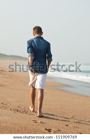 Young adult caucasian male walking on the beach - stock photo