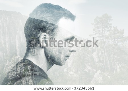 Young adult Caucasian man, profile portrait combined with mountain forest landscape, double exposure photo effect - stock photo