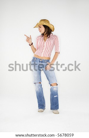 Young adult Caucasian woman wearing cowboy hat pointing finger like a gun. - stock photo