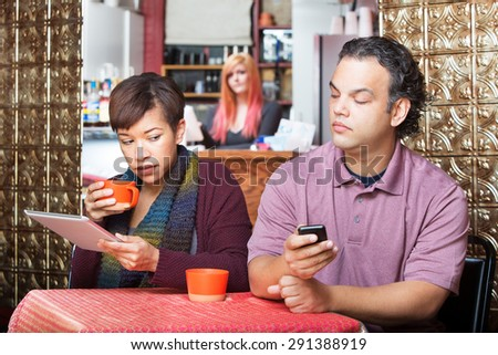 Young adult couple at cafe sneaking a peek at their devices - stock photo
