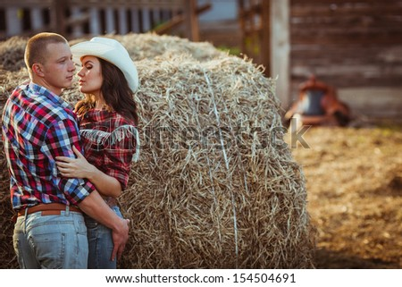 young adult couple embracing near hay - stock photo