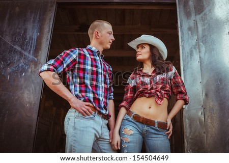 young adult couple standing near stable - stock photo