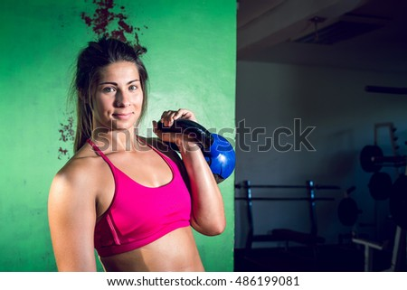 Young adult crossfit girl holding kettlebell