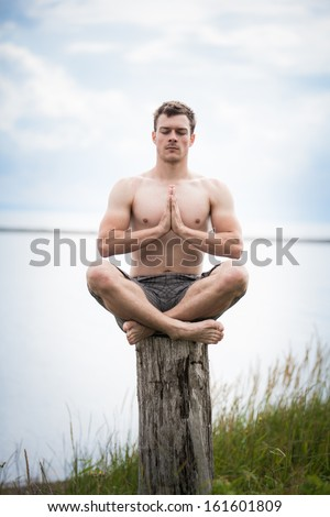 Young Adult Doing the Sukhasana (Easy position) in Yoga on a Stump in Nature - stock photo