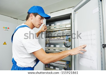 Young adult electrician builder engineer inspecting electric counter equipment in distribution fuse box - stock photo