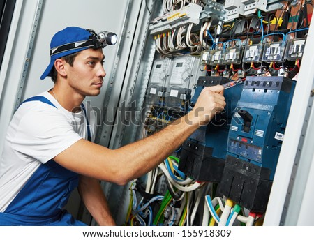 Young adult electrician builder engineer screwing equipment in fuse box - stock photo