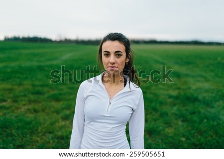 Young Adult Female Runner standing in grass field in country - stock photo