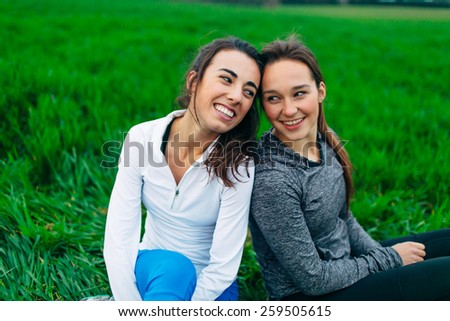 Young Adult Female Runners sitting in grass field smiling towards each other - stock photo