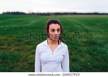 Young Adult Female standing in grass field near sunset - stock photo