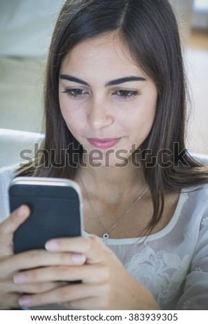 Young adult female using cell phone. Indoors close up.