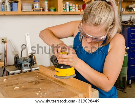 Young adult female woodworker sanding plank with electric sander - stock photo
