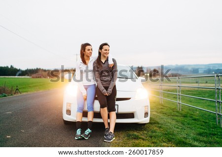 Young Adult Females resting on car after run with lights on