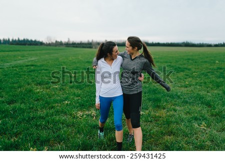 Young Adult Females Walking in Country grass field - stock photo