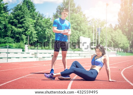 Young adult fitness woman posing outdoors at athletic track with her personal trainer. - stock photo