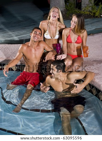 Young adult friends laughing together by swimming pool - stock photo