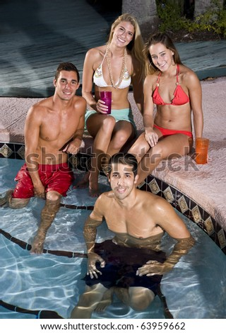 Young adult friends relaxing together by swimming pool - stock photo