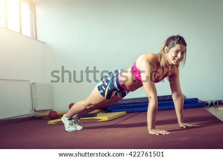 Young adult girl doing push ups exercise in gym - stock photo