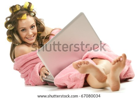 Young adult girl in pink dressing gown and with hair rollers sitting with laptop - stock photo