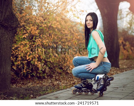 Young adult girl kneeling on roller skates in park during autumn season. - stock photo