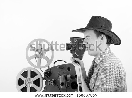Young adult handsome caucasian male videographer holding a videography old retro style camera on gray background White and black film  - stock photo