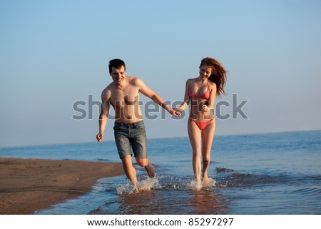 young adult happy couple running on beach