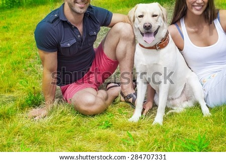 Young adult happy Couple sitting with white Dog Labrador at summer park on fresh green grass background against spring trees in perspective Empty copy space for inscription