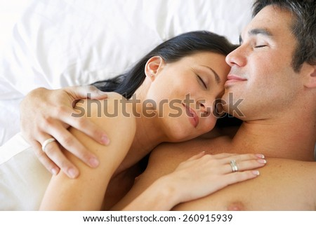 Young adult heterosexual couple lying on bed in bedroom - stock photo