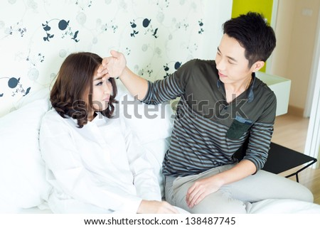 Young adult husband takecare his sick wife in bedroom - stock photo