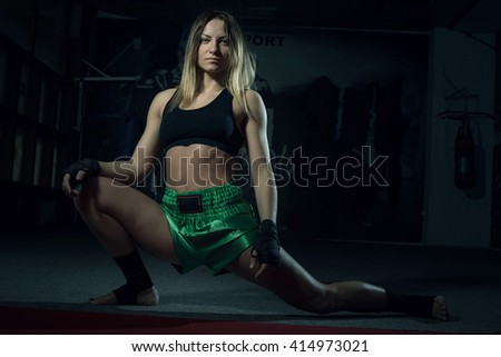 Young adult kickboxing girl stretching her body and doing splits