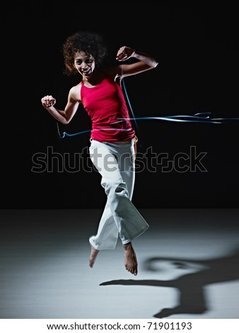 young adult latin american female jumping and playing with led lights doing streaks on black background. Vertical shape, full length, front view, copy space - stock photo
