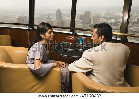 Young adult male and female seated near window in a high rise restaurant. They are smiling at one another. Horizontal shot. - stock photo