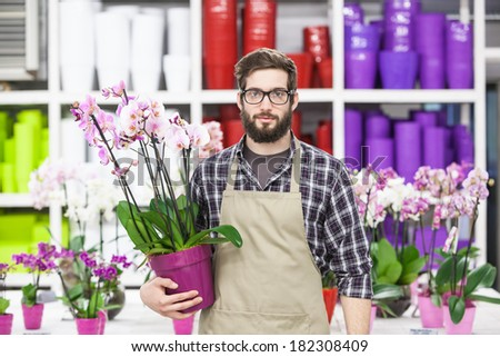 Young adult male florist at greenhouse - stock photo