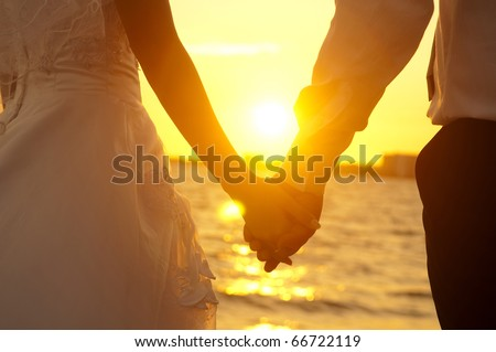 Young adult male groom and female bride holding hands on beach at sunset. - stock photo