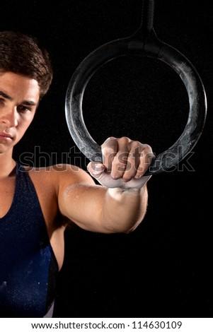 Young adult male gymnast. Studio shot over black. - stock photo