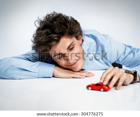 Young adult male plays with red toy car and having fun / photos of immature man wearing  blue shirt over gray background - stock photo