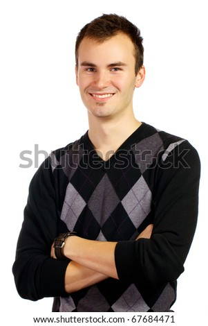 Young adult male standing with his arms crossed looking confidently into the camera with a smile across his face. - stock photo