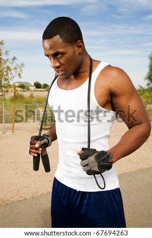 Young adult male with jump rope ready for a fitness workout - stock photo