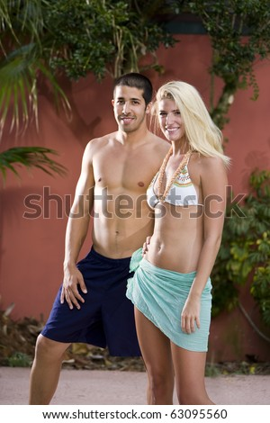 Young adult man and woman standing in relaxed pose, looking at camera