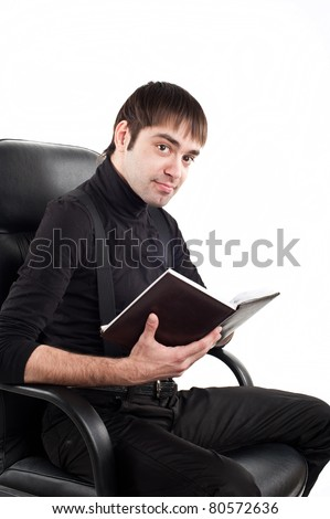 young adult man belonging to the Caucasoid race, wearing a black sweater sits in a leather director's  chair with a notepad and thinks isolated over white image,office work,clerc in chair - stock photo